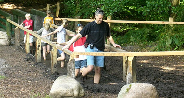Ein Gruppenführer mit einer Gruppe Kinder beim durchwaten eines Schlammweges