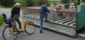 Zwei Leute laden Fahrräder auf Anhänger