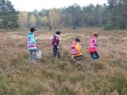 Vier Kinder laufen über eine Heide