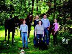 Gruppenbild im Grünen mit Pferden und Hunden